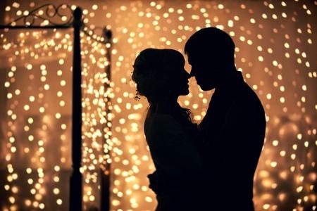 luna de miel: amantes de abrazos en silueta contra el fondo de guirnaldas de luces