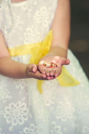 oneness: a child in a white dress holding a wedding ring