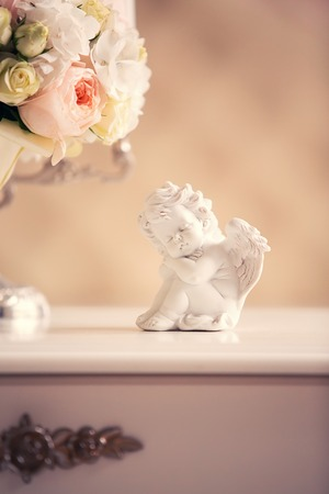 dresser: statue of an angel and a bridal bouquet on the dresser in the interior