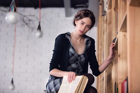 table skirt: Beautiful female student on stairs puts books in the library