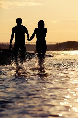 siluetas de enamorados: Los amantes a pie al atardecer en el río en la silueta Foto de archivo