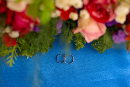 weddingrings: wedding rings in an environment of flowers on blue fabric