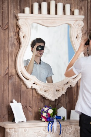 the photographer with the camera is reflected in a mirror