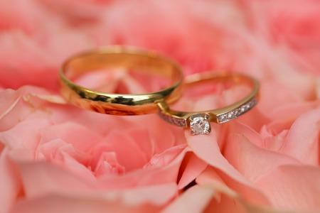 anniversario matrimonio: anelli di nozze d'oro sulle rose Archivio Fotografico