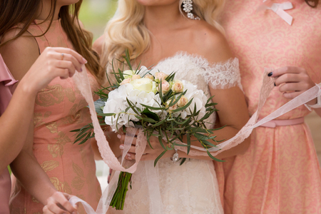 bridesmaids: bridesmaids in pink dresses with a bouquet
