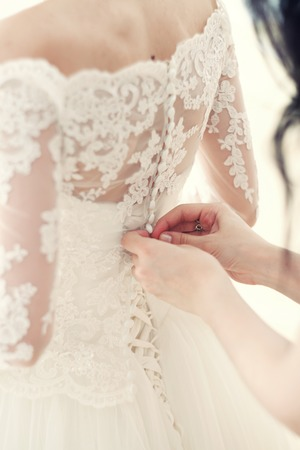 clasps: the hand of the girlfriend clasps buttons on the brides corset Stock Photo
