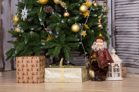 toygift: Santa Clauss figure and gifts under a fir-tree for Christmas