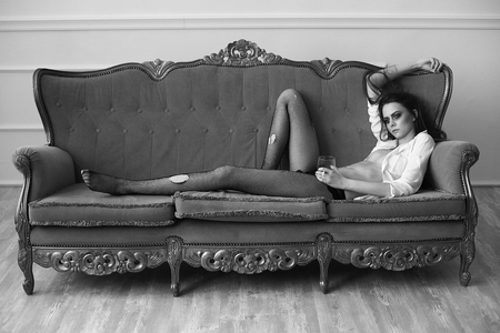 beautiful girl in fragmentary stockings lies on an ancient sofa