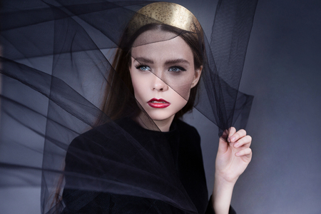 the beautiful girl with a black veil on a face, red lips and a gold crown
