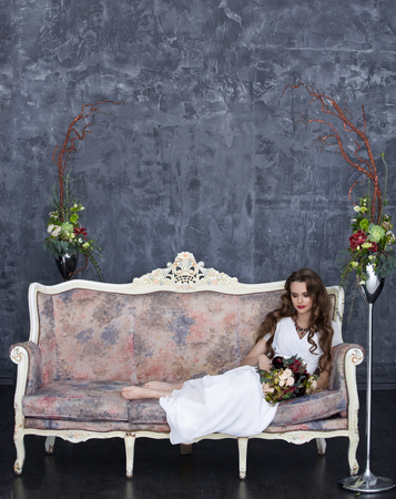 stylish bride sits on a vintage sofa and holds in hand a bouquet from succulents
