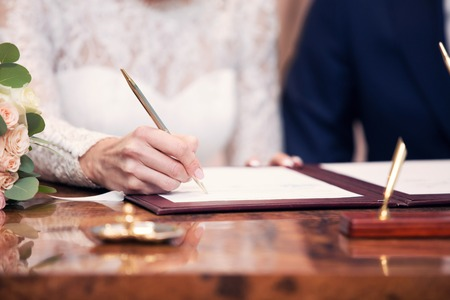 append: newlyweds append signatures in a registry office during wedding registration Stock Photo
