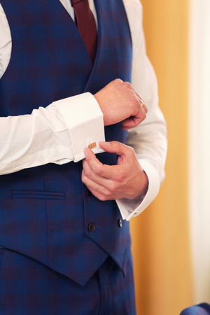 cuffs: the man in a red tie clasps cuff links on shirt cuffs
