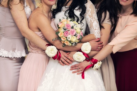 helpmate: bridesmaids with bracelets in the form of flowers embrace brides