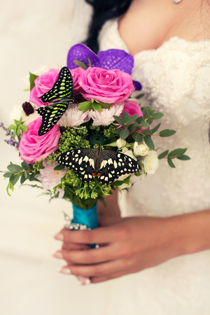 color in: bridal bouquet of pink color in hands with butterfly