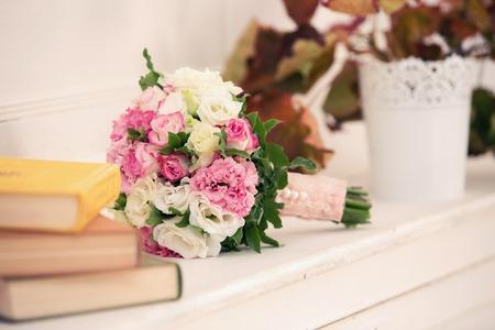 Brautstrauß aus Rosen von rosa Farbe und ein Stapel der Bücher