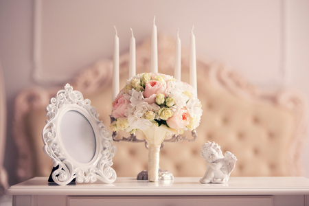 bridal bouquet with peonies on a table with a vintage mirror and an angel