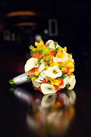 calas blancas: orange bridal bouquet with white callas on a table