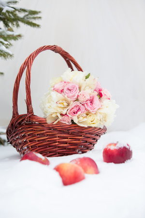 wattled: bridal bouquet from roses of pink color in a wattled basket on snow and red apples