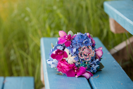 costume jewelry: bridal bouquet with orchids of violet and pink color with costume jewelry against a grass