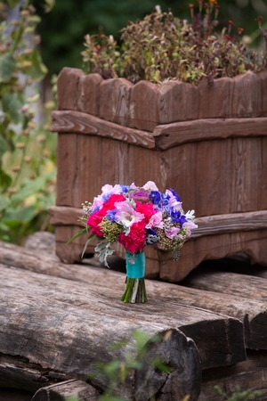day bed: bright bridal bouquet of red and violet color on wooden boards Stock Photo