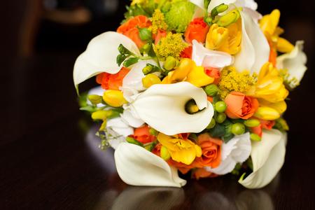 calas blancas: ramo de novia de color naranja con callas blancas en una mesa
