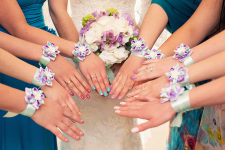 wedding bouquet: bride and bridesmaids with violet bracelets on hands Stock Photo
