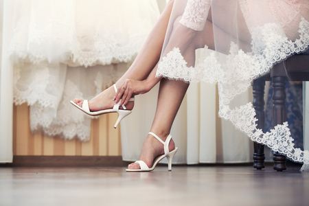 the bride puts on white shoes on feet