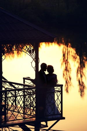 arbor: kiss lovers in an arbor against the lake at sunset