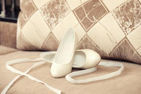 weiße Schuhe der Braut und des beige Sofas