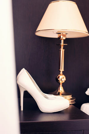 foot gear: white shoes of the bride on dark furniture and the lamp