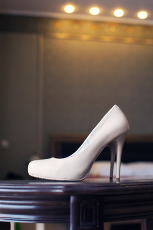 foot gear: white wedding shoes on dark wooden furniture Stock Photo