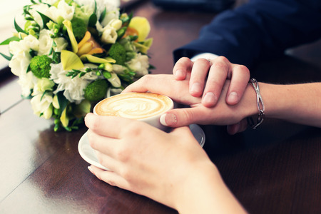 valentina: hands of the groom and the bride hold a cup of coffee Stock Photo