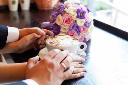 valentina: hands of the man and the woman and a cup of coffee with foam in the form of heart