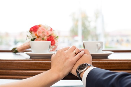 amorousness: newlyweds in cafe drink coffee behind a show-window Stock Photo