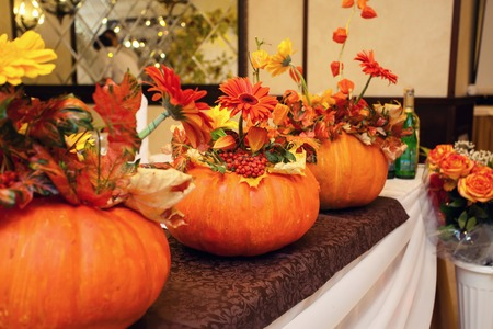 wedding table decor: autumn decor in the form of pumpkins and red flowers