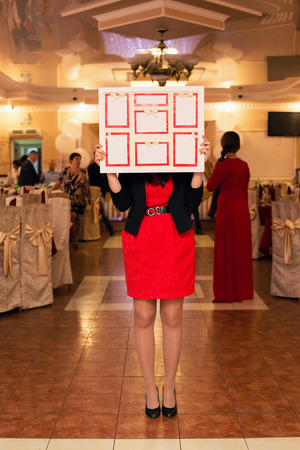 wedding reception decoration: the girl stands in the center of restaurant and holds the plan of seating of guests