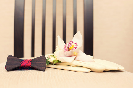 buttonhole: wooden  bow tie of a glove and a buttonhole from an orchid Stock Photo