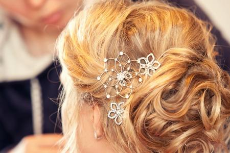 젊은 금발의 여자와 보석 머리핀은 여자의 머리카락에
