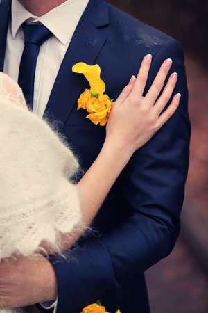buttonhole: bride presses down the groom in a white suit and a yellow buttonhole
