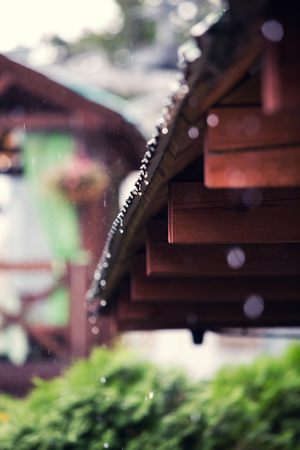 trickle down: rain drops on a roof of the wooden house Stock Photo