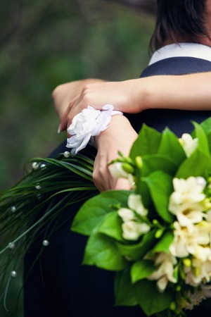 a bracelet: the bride with a white bracelet and a green bouquet in hands embraces strong the groom