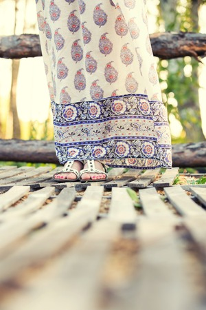 russian girls: the girls feet in a beautiful Russian sundress on the wooden bridge