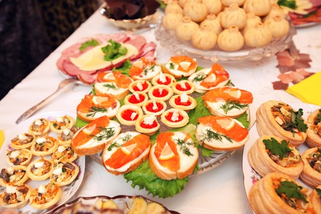 banquet table: Beautifully decorated catering banquet table with different food snacks and appetizers with sandwich, caviar, fresh fruits Stock Photo