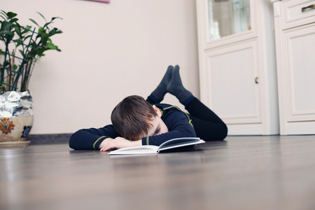 Image of young boy sleeping near books in the living room