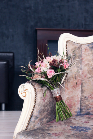 threw: bridal bouquet of pink color on a vintage sofa Stock Photo