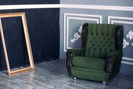 stylish chair: stylish interior in dark tones. Green chair and gold frame Stock Photo