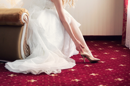 claret: the bride puts on elegant wedding shoes. Claret color. Morning of the bride Stock Photo