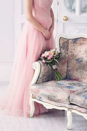 Stock Photo   The Bride In A Pink Wedding Dress And A Vintage Sofa In A  White Interior. A Bridal Bouquet From Pink Roses On A Sofa