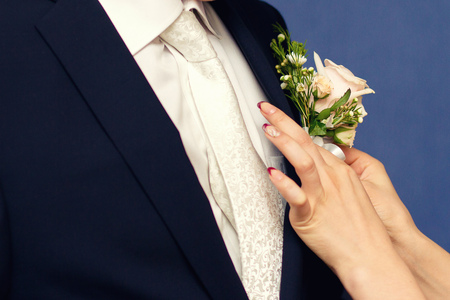 buttonhole: hands of mother correct a buttonhole for the groom
