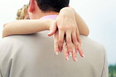 bridegrooms: Bride embraces bridegrooms neck rear view.